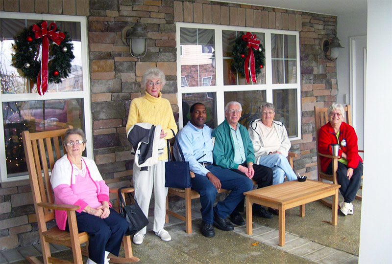 Elderly people sitting on front porch