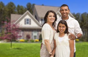 Hispanic family standing in front of house.
